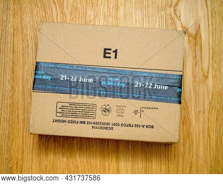 Paris, France - June 21, 2021: Pov Male Hand Holding Amazon Parcel Cardboard With Special Markings O