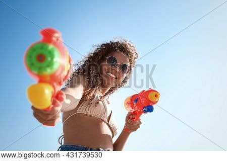 African American Woman With Water Guns Against Blue Sky, Low Angle View