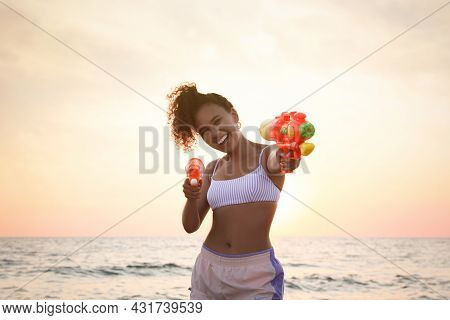 African American Woman With Water Guns Having Fun On Beach At Sunset