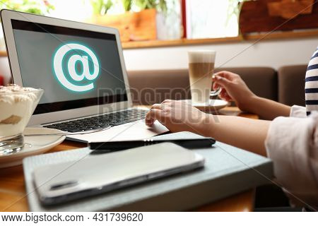 Woman Sending Email Via Laptop In Cafe, Closeup