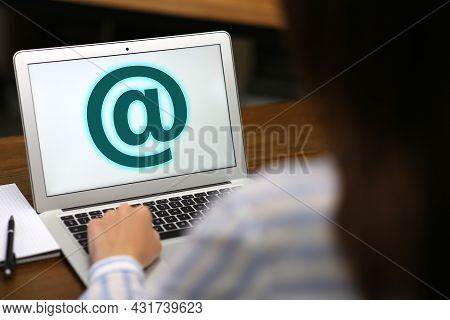 Woman Sending Email Via Laptop At Table, Closeup