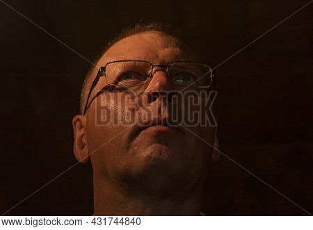 Mature Man In Glasses Looking Up To Light From Sky. Spiritual Insight Concept.