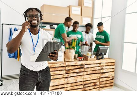 Group of young african american volunteers working at charity center. Man smiling happy talking on the smartphone.