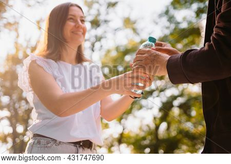 Volunteer Young Woman Serving A Bottle Of Water For Poor People Outdoors, She Helps To Quench Their