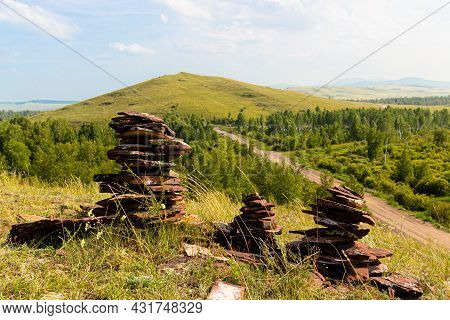 Three Cairns From Reddish Balanced Stones Of Devonian Sandstone On The Top Of Hill Against Summer Mo