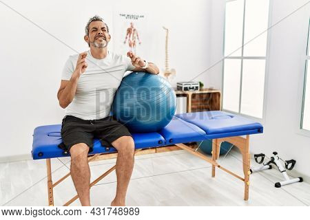 Middle age hispanic man at pain recovery clinic holding pilates ball gesturing finger crossed smiling with hope and eyes closed. luck and superstitious concept.