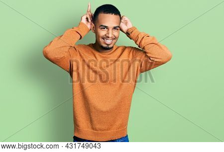 Young african american man wearing casual clothes posing funny and crazy with fingers on head as bunny ears, smiling cheerful