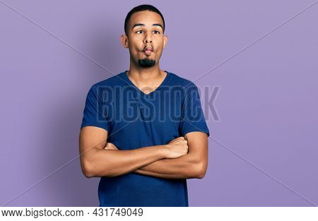 Young african american man with arms crossed gesture making fish face with mouth and squinting eyes, crazy and comical.