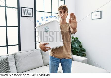 Young caucasian man holding wastebasket with recycling plastic bottles at home with open hand doing stop sign with serious and confident expression, defense gesture