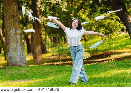 Close Up Photo Of A Happy Young Woman Activist Being Outdoors Throwing The Medical Masks And Protest