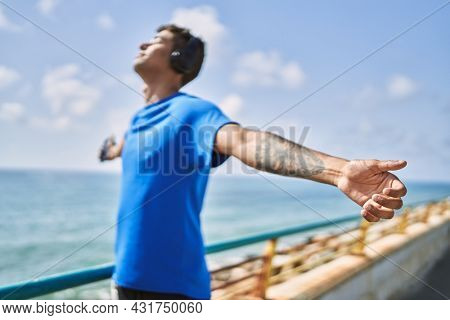 Young latin man breathing using headphones and smartphone at the beach.