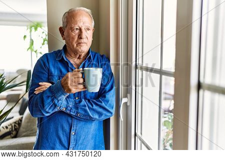 Senior man with grey hair leaning by the window of his home, drinking a cup of coffee in the morning
