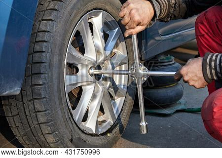 The Repairman Unscrews The Wheel For Replacement With A Wheel Wrench. Seasonal Change Of Car Tires.