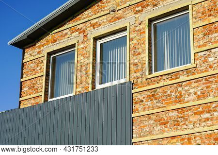 Cladding Of A Brick House Facade With Corrugated Sheet Metal