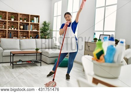 Young chinese housewife smiling happy singing and dancing using mop at home.