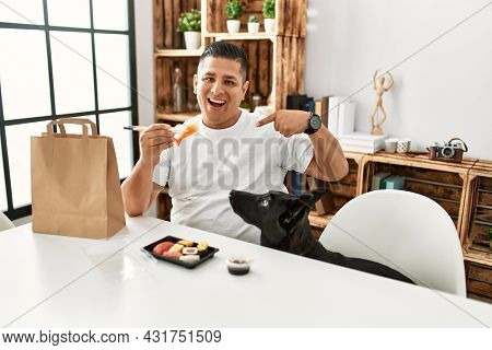 Young hispanic man eating sushi using chopsticks pointing finger to one self smiling happy and proud