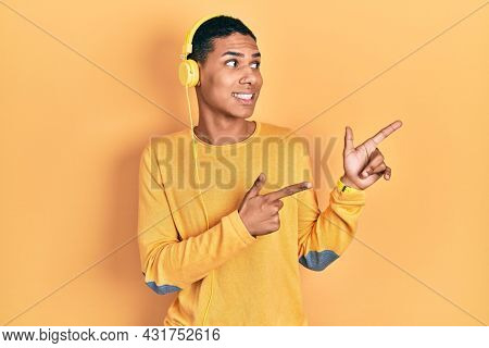 Young african american guy listening to music using headphones pointing aside worried and nervous with both hands, concerned and surprised expression