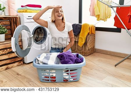 Young caucasian woman doing laundry with clothes in the basket very happy and smiling looking far away with hand over head. searching concept.
