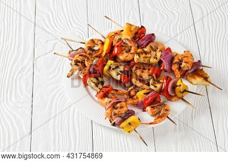 Pineapple Shrimp Kabobs With Charred Red Onion, Sweet Pepper On A White Plate, On A Wooden Table
