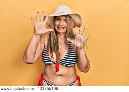Middle age hispanic woman wearing bikini and summer hat showing and pointing up with fingers number ten while smiling confident and happy.