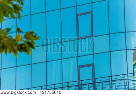 Beautiful View Of The Mirrored Blue Windows Of The Facade Of The Building Against The Background Of