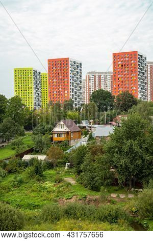 A Wooden House, A River, Green Trees Against The Background Of Bright Multi-storey Houses Of Yellow