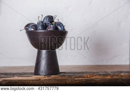 Plums In A Clay Handmade Vase On Wood With White Loft Background. Craft