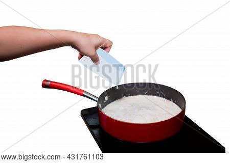 A Person's Hands Are Pouring The Milk From The Carton Into The Spaghetti Sauce Pan Set On The Induct