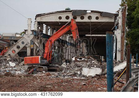 Orange Excavator Demolishes An Old Industrial Building.