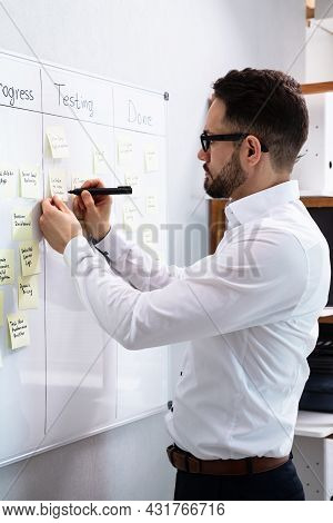 Man Writing Notes On Kanban Board In Office