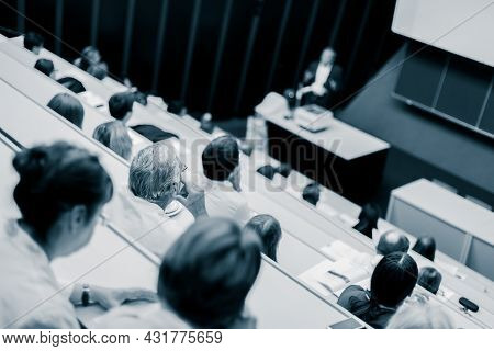 Professor Giving Presentation In Lecture Hall At University.