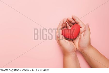 Little Boy Hand Holding Red Heart On Pink Background, Health Care, Love, Organ Donation, Family Insu