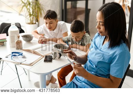 Black woman doctor using tablet computer while sitting at table with her sons in home