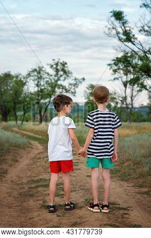 Two Little Children Holding Hands. Boys Brothers Travel On Road. Full Length. Back View. Authentic L