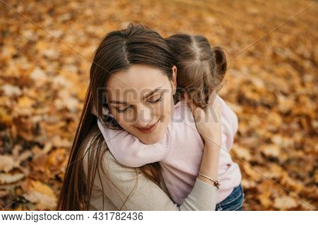 Mothers Love, Moms Love. Close Up Portrait Of Embracing Mom And Toddler Baby Daughter In Autumn Park