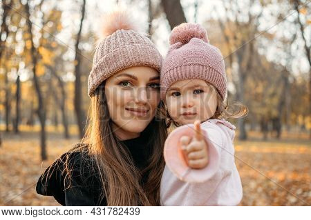 Close Up Portrait Of Mom And Toddler Baby Daughter In Autumn Park With Baby Stroller. Happy Family M
