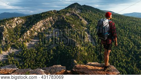 A Male Tourist With A Backpack Admires The Sunset From The Top Of The Mountain, Panorama. A Traveler