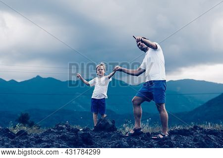 Father Son Or Adult Younger Brother Walk. Cloudy Sky Before Rain, Mountain Background. Man Show Poin