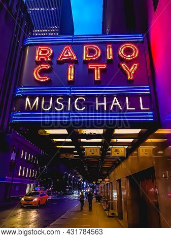 Radio City Music Hall Marquee Colorful Neon Sign In Nyc During Twilight Hours Near Buildings. People