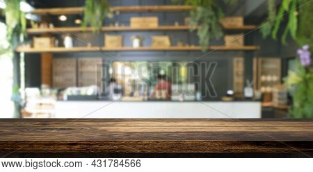 Empty Wooden Table Top With Abstract Blurry Image Of Coffee Shop Or Cafe Restaurant In Background Fo