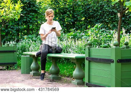 Young Pretty Blonde In White T-shirt Sits On Bench In Beautiful Garden With Her Legs Curled Up And H