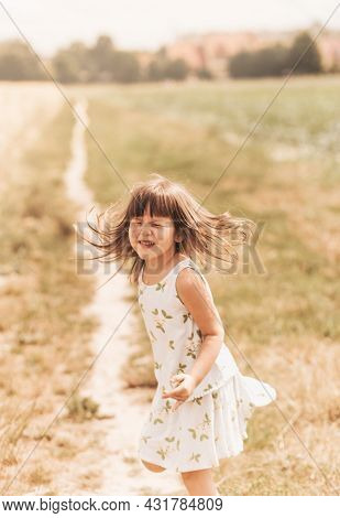 A Little Girl Runs Through A Wheat Field. The Girl Has Fun And Laughs With Delight. Field With Ripe