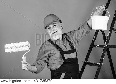 Painter Working At Construction Site. Senior Man Use Roller On Ladder. Work In Apartment. Craftsman