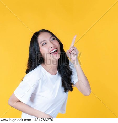 Beautiful Cute Asian Woman Smiling And Pointing Finger To Empty Copy Space , Blank Space For Adverti