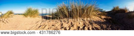 Panorama Of A Sand Dune At The Beach Of Koksijde  In Flanders In A Warm Autumnal Light With A Glimp