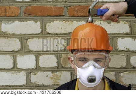 A Construction Worker In A Protective Construction Helmet, A Respirator And Protective Glasses On Th