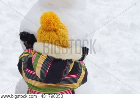 A Little Girl In A Winter Jumpsuit Plays In The Snow In Winter And Makes A Snowman Out Of Snow