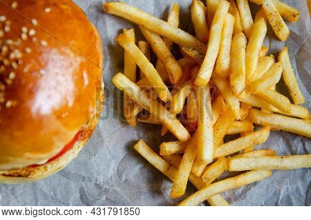 Fried Fries And Blurred Hamburger Background. Unhealthy Food Concept. Delicious Fast Food. Juicy Bur
