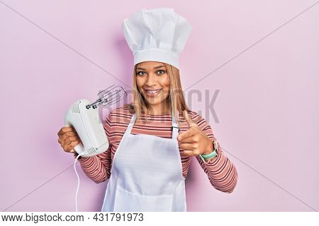 Beautiful hispanic woman holding pastry blender electric mixer pointing fingers to camera with happy and funny face. good energy and vibes.