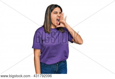 Young hispanic girl wearing casual purple t shirt shouting and screaming loud to side with hand on mouth. communication concept.